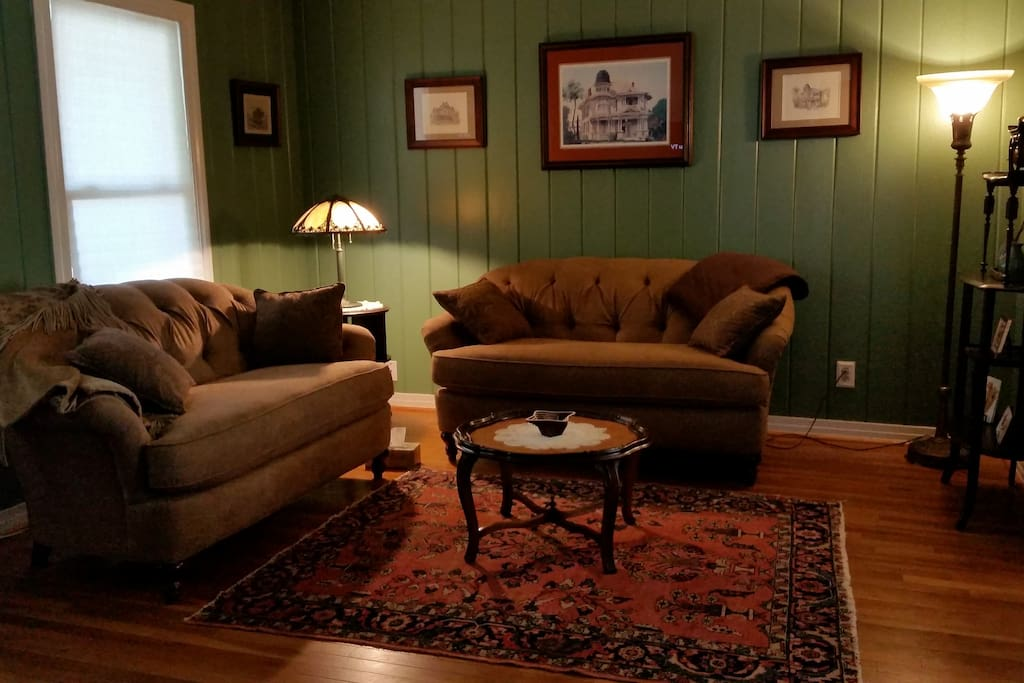 Living Room furnished with custom made love seats, antiques and original artwork