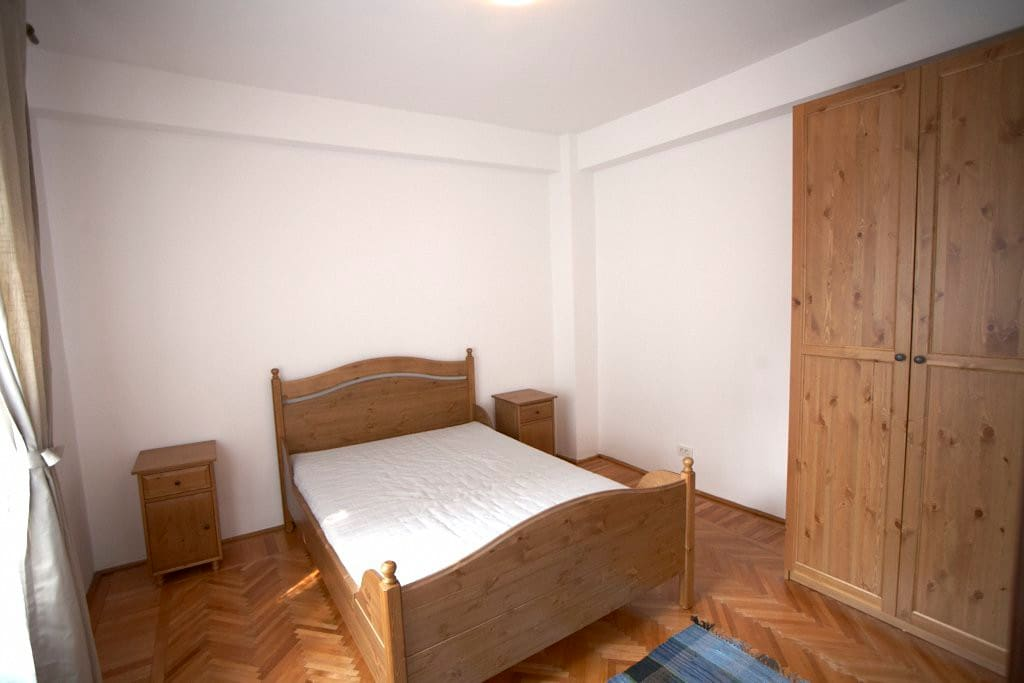 Bedroom One: It has a retro style, with solid wood furniture complementing the hardwood floor.