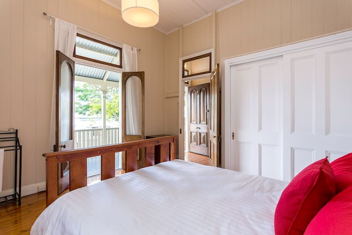 Queen size bed with French doors opening to the front veranda