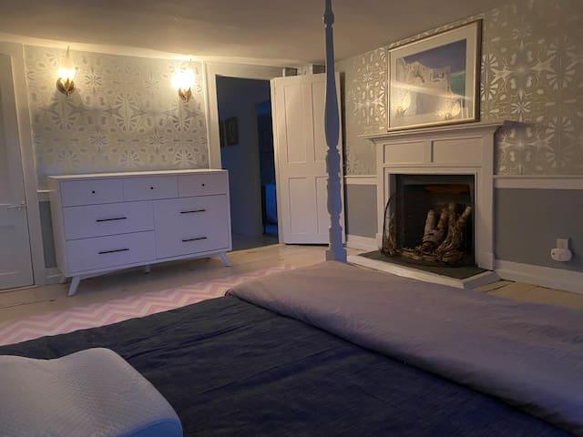 Second floor bedroom queen sized bed next to master bedroom.