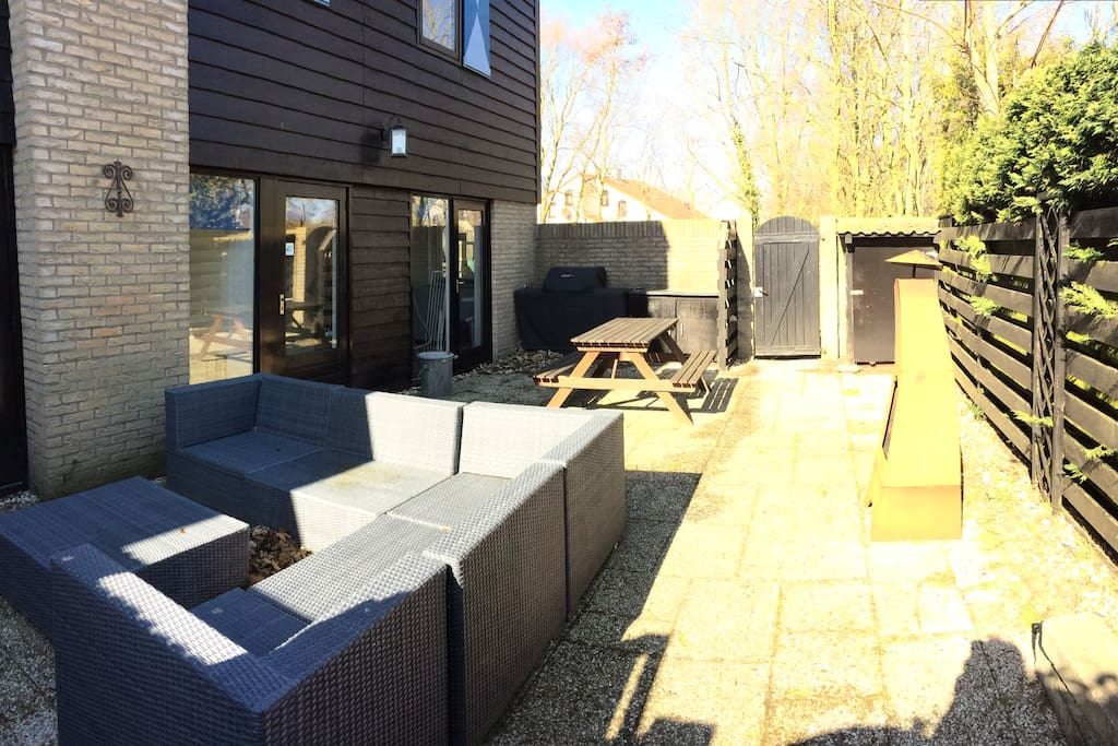 De patio vol privacy, met gezellige haard, loungeset, tuinverwarming en gas BBQ.