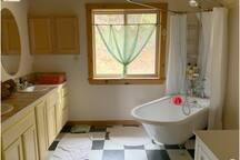 Large Private Bathroom with deep clawed foot iron soaking bathtub, shower and telephone style bath spray.