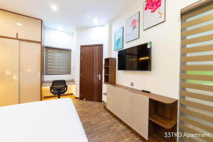 Bedroom of 3B apartment; 43 inch  smart TV - brand SamSung, and the wall paintings, and A work and makeup table with swivel chair.