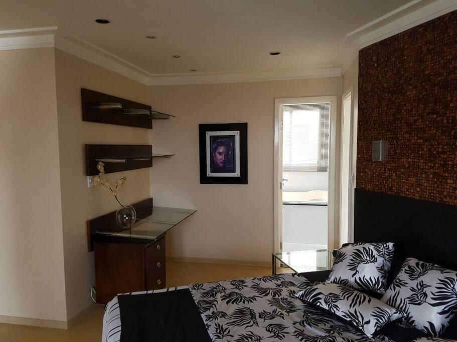 Quarto mobiliado e decorado, porta de acesso ao banheiro