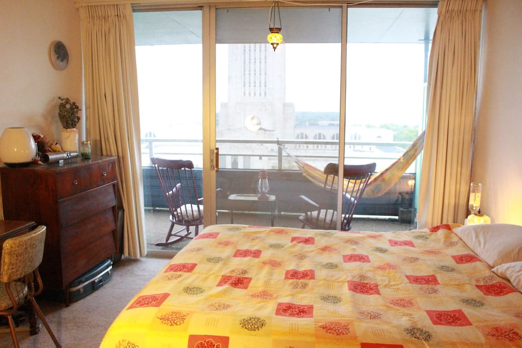 View of the estate capitol from bedroom with sliding glass door to rocking chairs and hammock