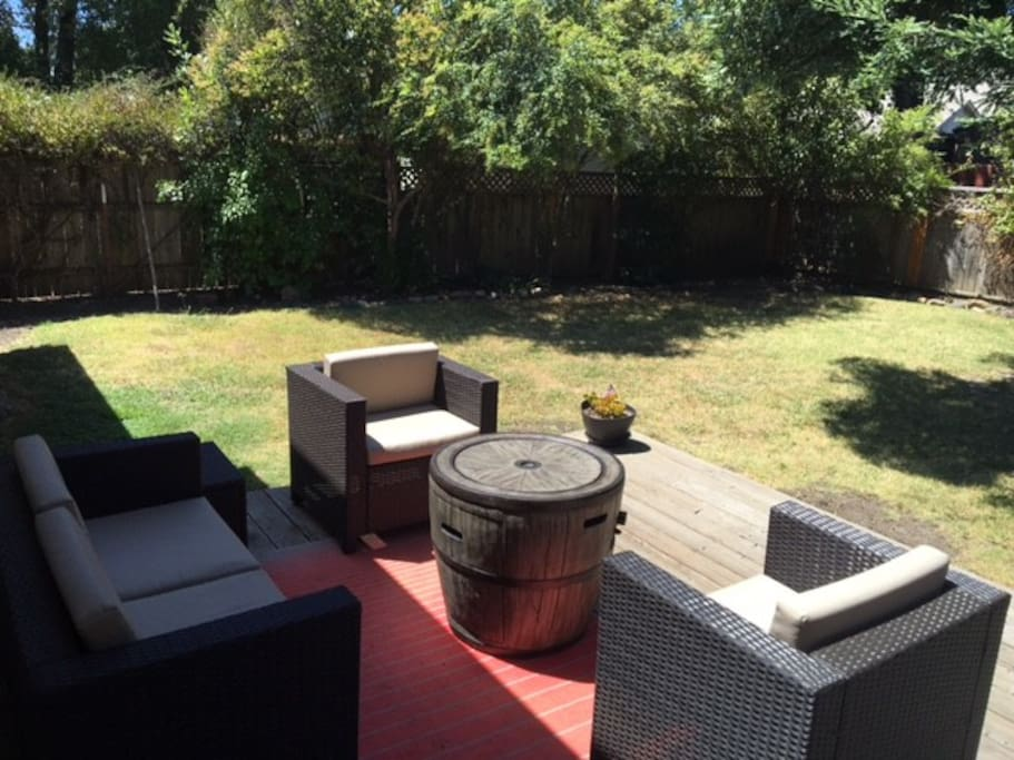 Backyard deck with lounge chairs, wine barrel fire table and gas BBQ. Perfect spot for post wine tasting evening drinks