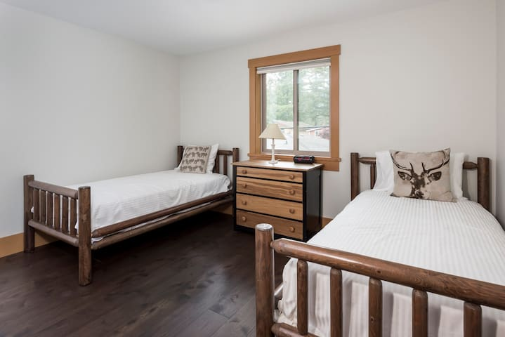 Two custom wood frame twin beds with hotel quality linens