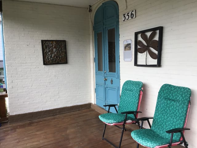 The porch is a shared spot for yourself and other guest to enjoy. The large double blue doors, original to the house, led to your studio.