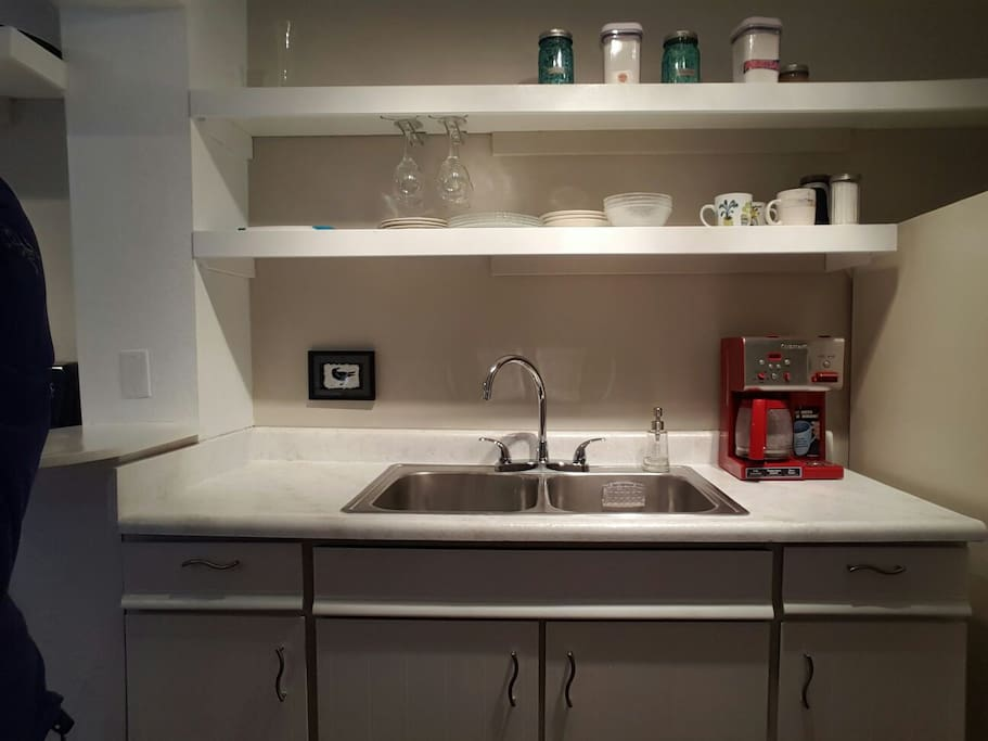 Kitchen features new shelving, counter top, sink faucet, and coffee maker. Help yourself to the complimentary coffee and breakfast fixings.
