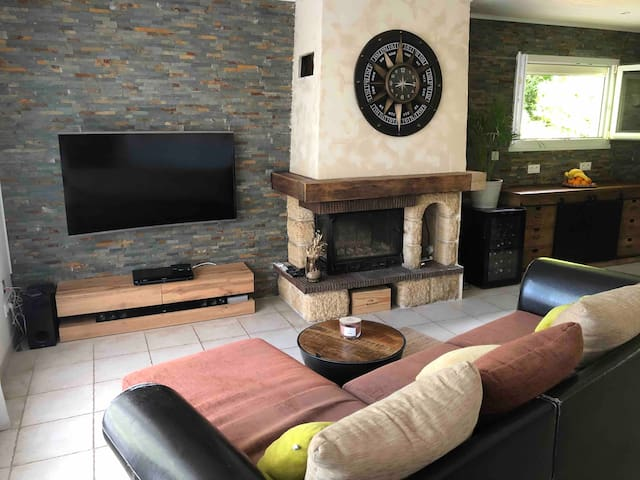Salon avec grande tv incurvée led.lecteur dvd et plusieurs dvd .. cheminée fonctionnelle . Le canapé se transforme en grand lit
