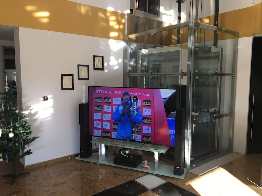"84"" big screen TV in front of panoramic elevator shaft"