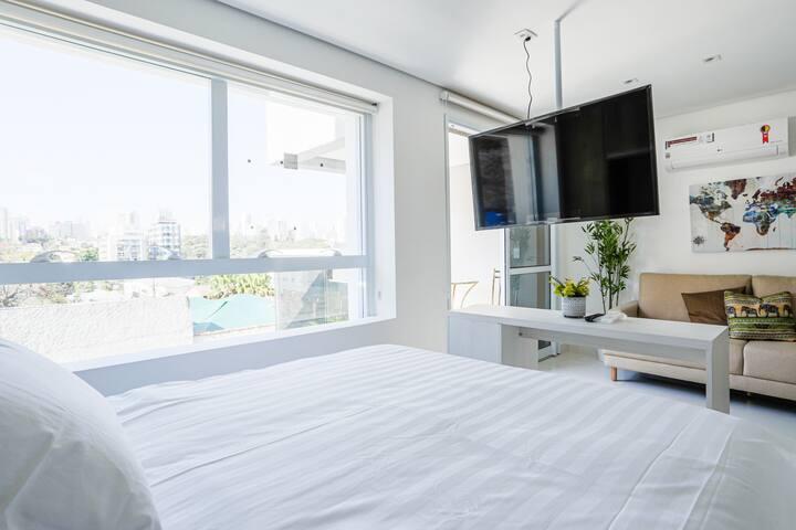 Studio moderno, completo, ar condicionado, varanda com mesa e cadeiras, TV smart, cama queen, sofá que acomoda mais uma pessoa, mesa de trabalho refeições.