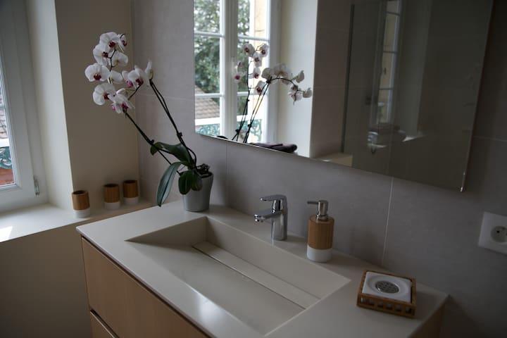 Salle de douche à l'étage avec meuble de salle de bain et sèche servietttes