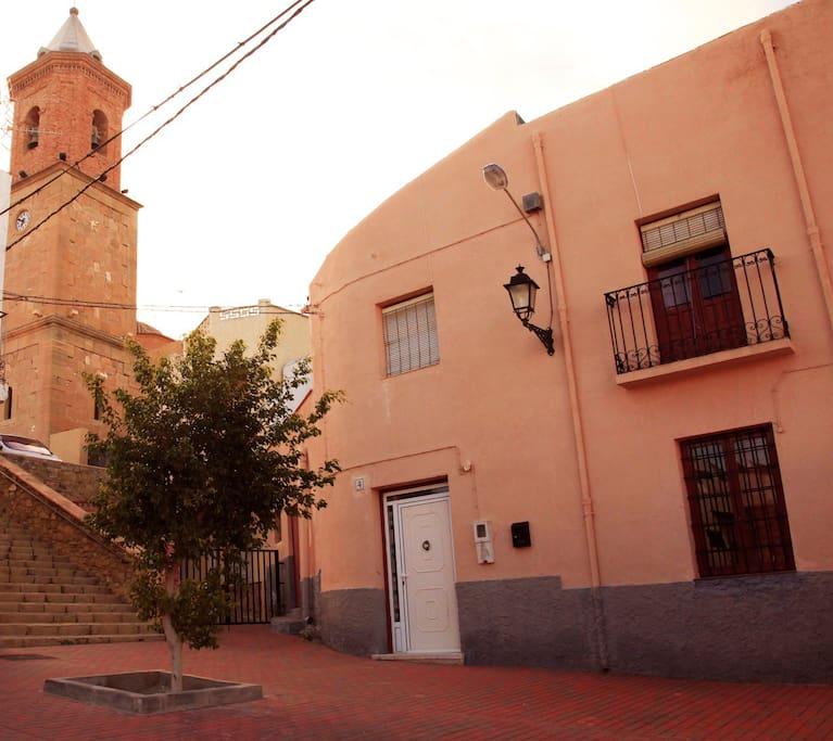 Fachada y entrada principal, se ve la iglesia del pueblo que está justo al lado, separada por una escalera.