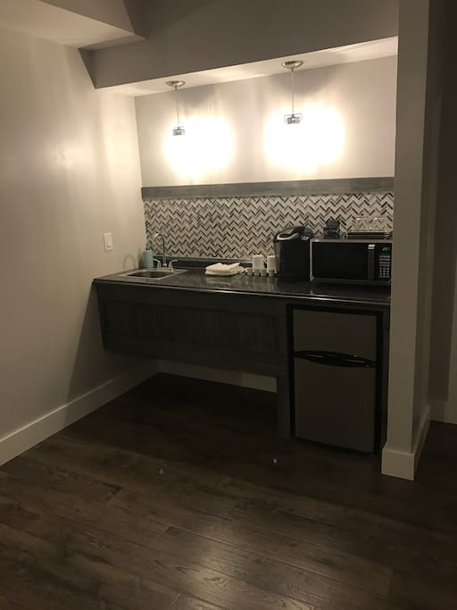 Wet bar with Keurig coffee maker, microwave, and mini fridge