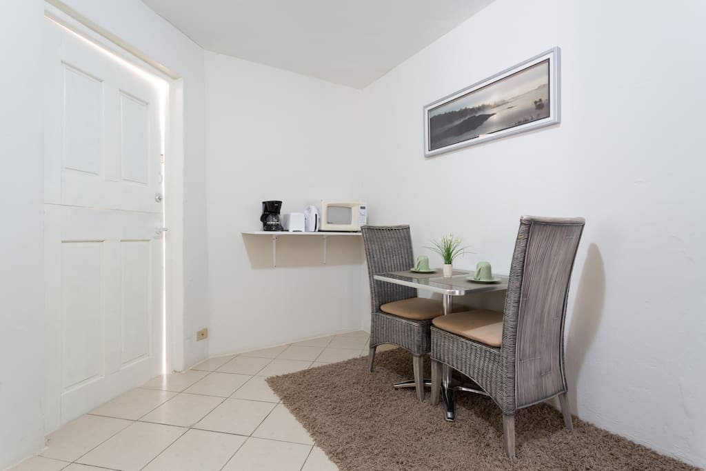 Small dining area . With microwave,  toaster, sandwich maker, coffee pot on the background.
