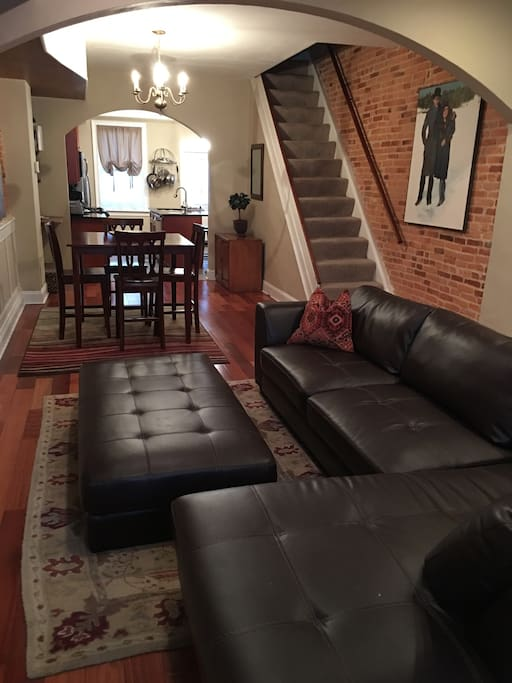 Open concept living/dining/kitchen with beautiful original architectural details, exposed brick and mahogany wood floors.