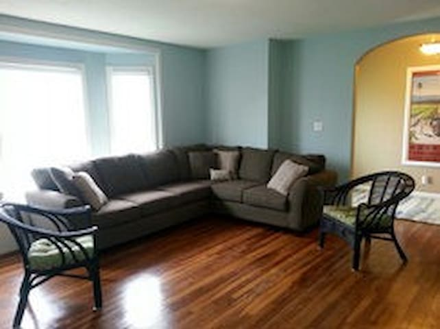 Front living space with large sectional couch with flat screen TV perfect for watching movies and game day!