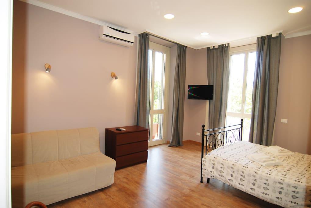 Vista della camera da letto tripla con letto matrimoniale e divano letto per 1 persona.