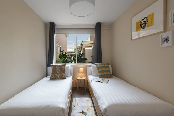 The second bedroom is perfect for the kids, complete with two single beds, a large window and more edgy artwork