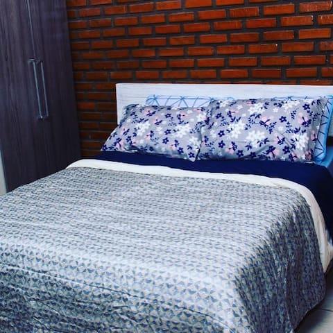 Quarto com cama de casal e duas de solteiro
