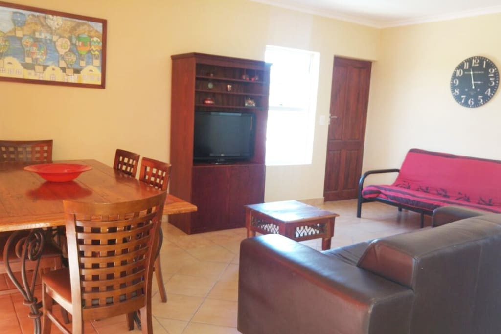 Lounge area with 6 seater dinner table and TV.