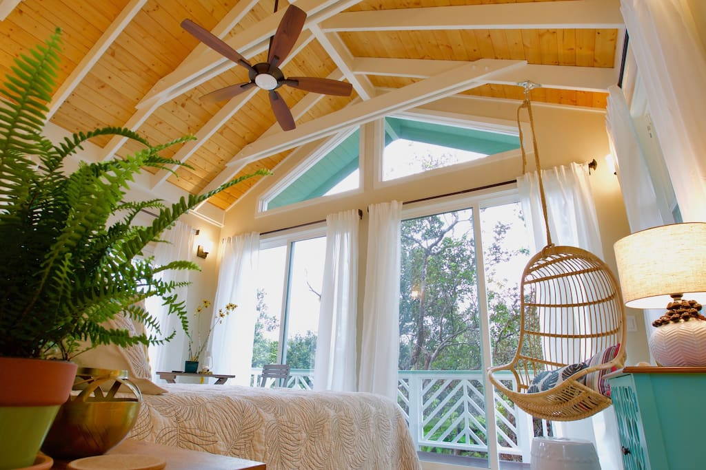 Large windows for an amazing view outside and loads of natural sunlight. Gorgeous wood ceiling with fan, large sliding glass doors and hanging chair for relaxing.