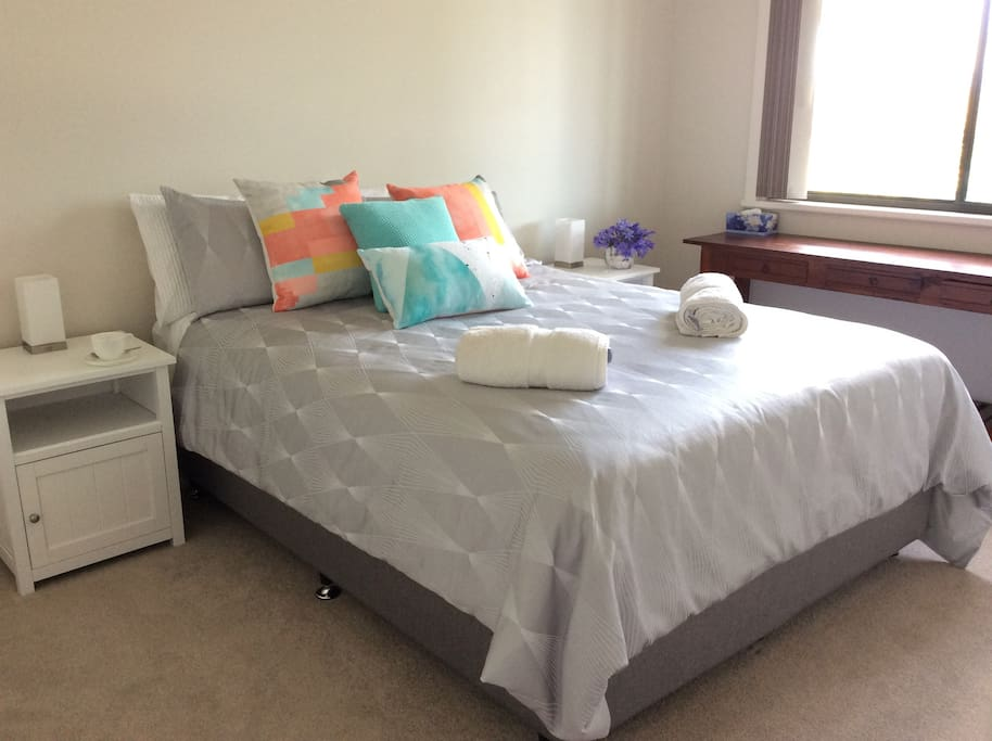 Queen bedroom with bedside tables and lamps, electric blanket, ceiling fan, built in robe bench for luggage.