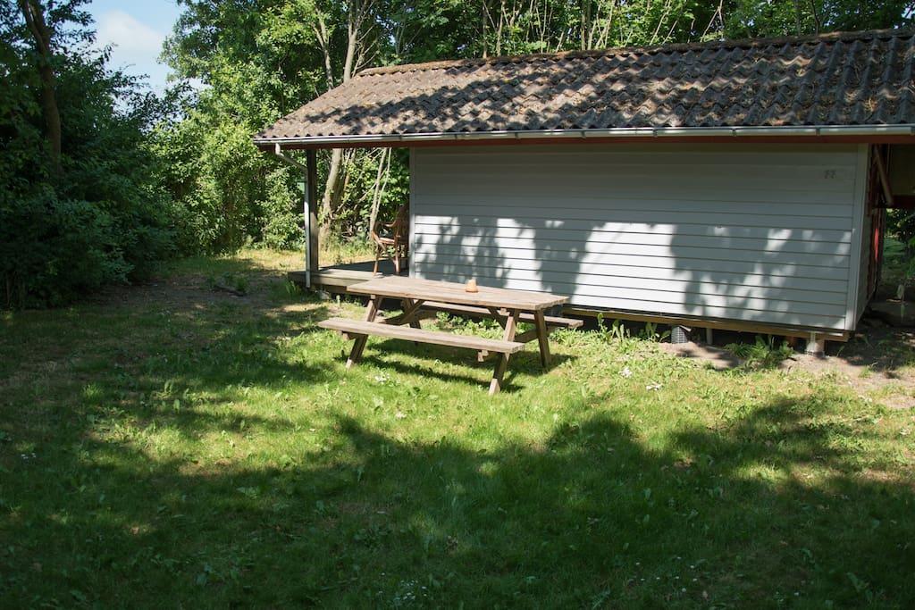 Plæne og træer omkring huset. Mulighed for at slå medbragt telt op her for at skabe soveplads til flere.