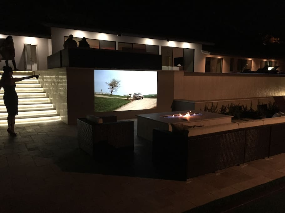 Outdoor Fire pit and with projecter and couches.