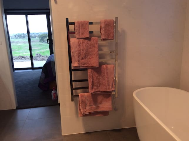 Private bathroom with heated towel rail, bath, double vanity and walk in shower.