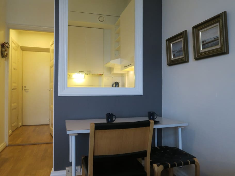 The working & eating table facing the internal window to the compact kitchen of this top floor one room + kitchen flat. Naturally seat by Artek, designed by the most famous Finnish architect and designer Alvar Aalto.
