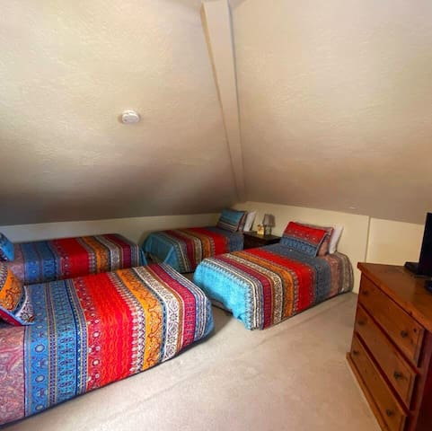 Loft bedroom. Four twin beds and space for sleeping bags if you have more children in your party.  Smart TV.