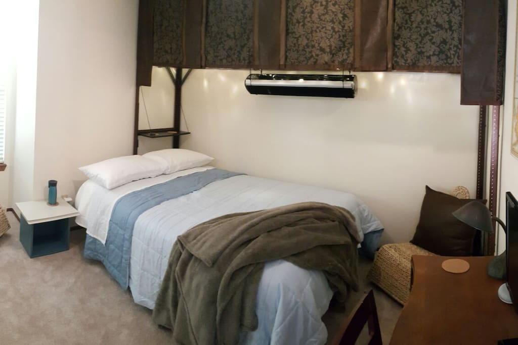 Wall outlet, with provided, 3-outlet USB adapter, between side table and bed.