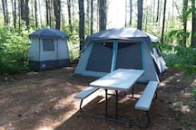Glamping tent,  privy tent, and picnic table.