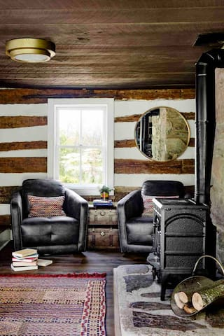 Another woodburning stove in the cabin room, with a cozy reading nook.  You can also see one of many vintage rugs throughout the home.  This one is from Morocco.