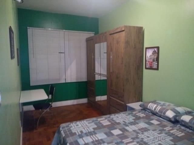 Dormitório com cama casal, mesa auxiliar e guarda-roupa (4 portas, 6 gavetas).