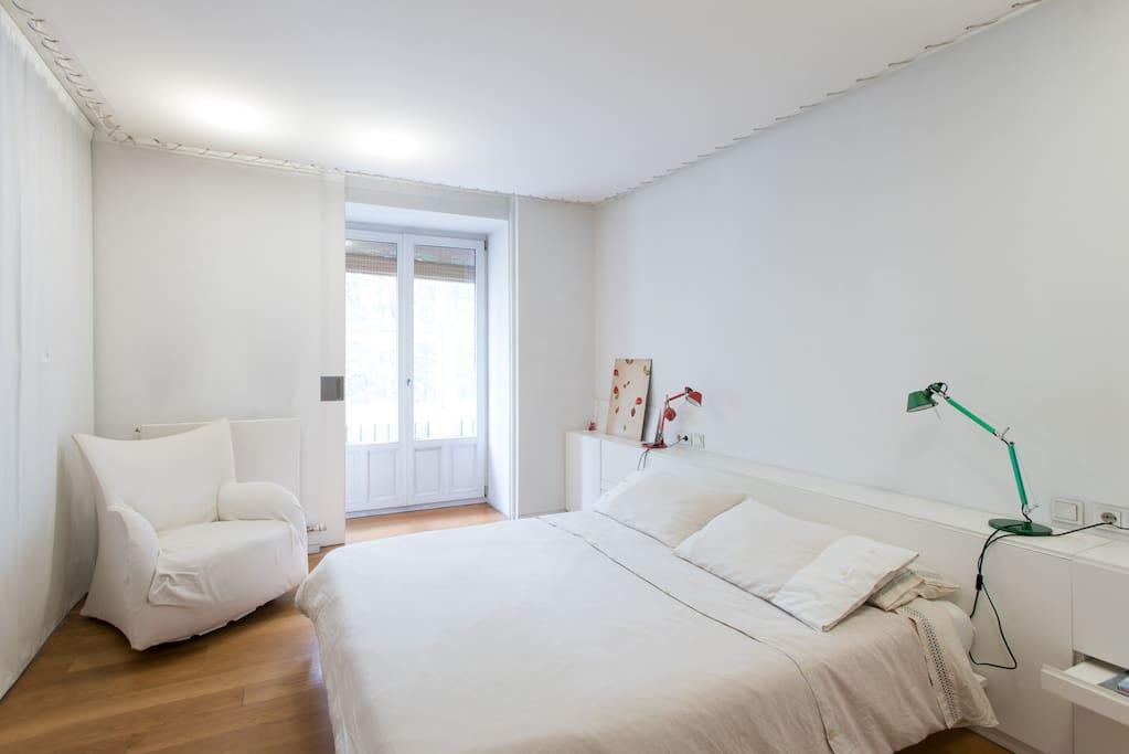 una habitación principal con baño incorporado y terraza