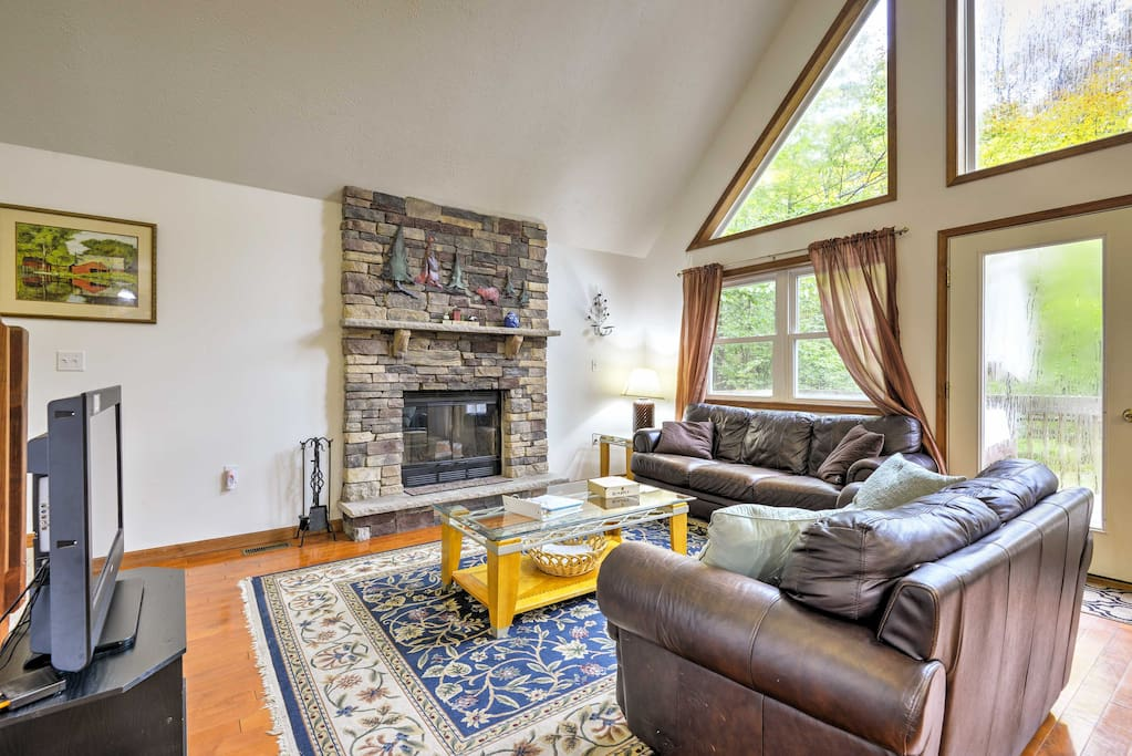 The open-concept living space features comfortable furnishings and a wood-burning fireplace.