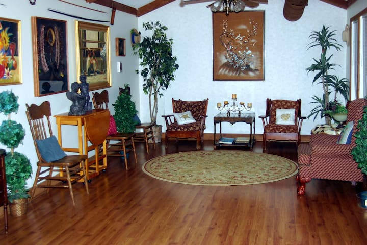 Spacious front sitting  room decorated with antiques, artifacts, and art.