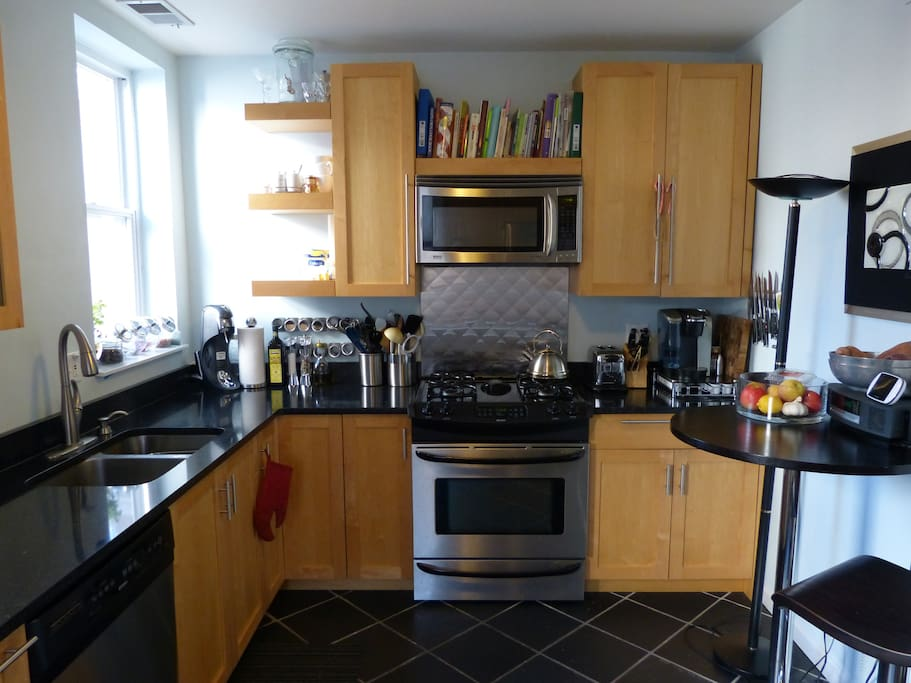 Gas stove, oven, microwave, toaster, coffee maker, dishwasher, and ample cabinet space.
