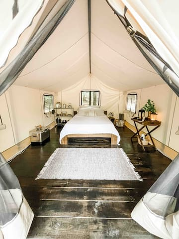 Spacious safari tent set up on a deck. All the essentials provided.