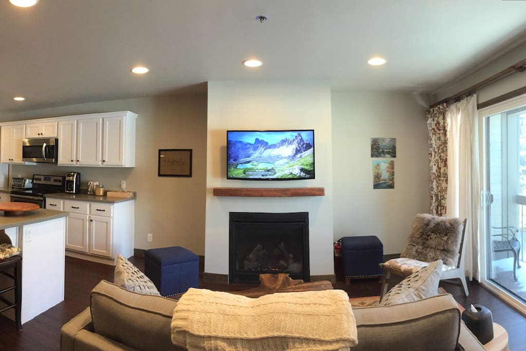 Upstairs great room with full kitchen and living room. Cozy fireplace, 4K TV and a view of the slopes out the window/sliding glass doors.