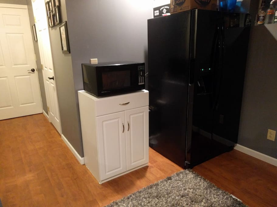 Refrigerator and microwave available for use (coffee-maker now sits on microwave), also a view of doors to the listing and bathroom.