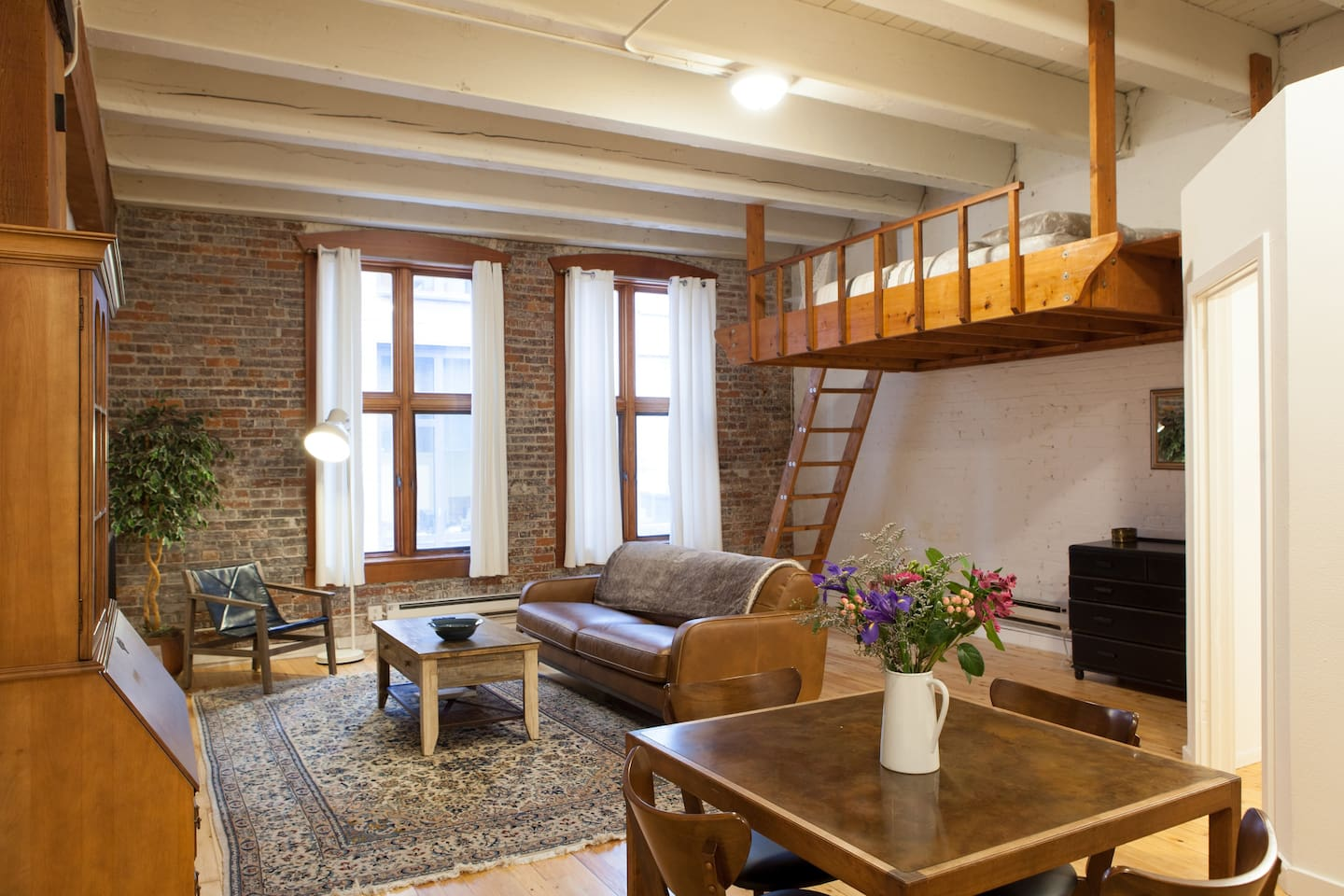 Gorgeous studio with high ceilings, original brick walls, leather sofa and chair, lofted custom-made queen bed, full kitchen, and spacious, well-appointed bathroom.