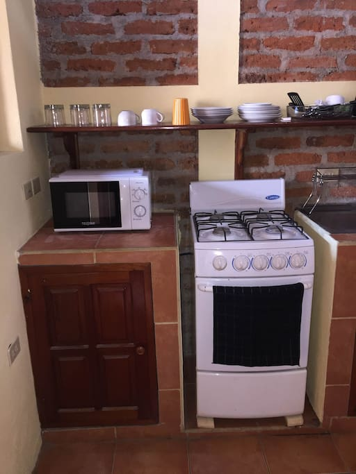 Microwave oven, cabinets, gas stove and oven.