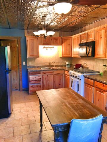 Fully furnished kitchen includes stove, refrigerator, microwave, coffee maker, and George Foreman grill