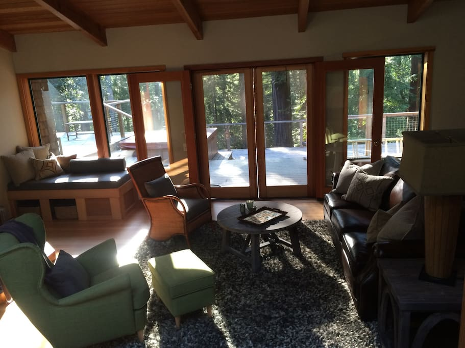 Another view of the living room, looking towards the back deck. The large deck includes a second bbq, hot tub, hammock, lounge chairs and seating.