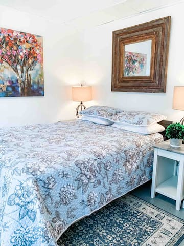The master bedroom offers a full sized mattress and has 2 side tables with hidden USB ports and additional electric plugins. French doors lead out to the back deck with an additional dining area, and views of the field.