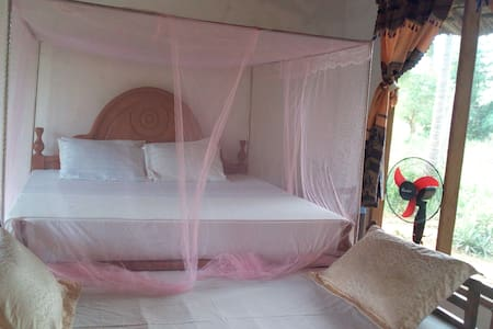 bed room with en suited bathroom running clean water, fan and mosquito net with enough space and sea view